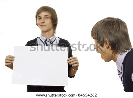 One boy looks surprisingly at another one holding a white poster