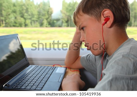 one boy watches movie on laptop in train