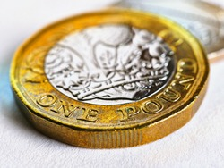 One British pound coin lies on a light white textured surface. Focus is on denomination of coin and name of currency of UK. Illustration about economy, money, finance in Great Britain. Brexit. Macro