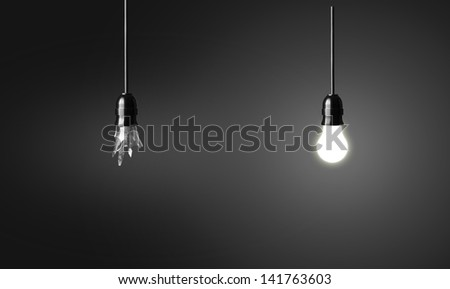 One broken and one glowing bulb. Idea concept on black background