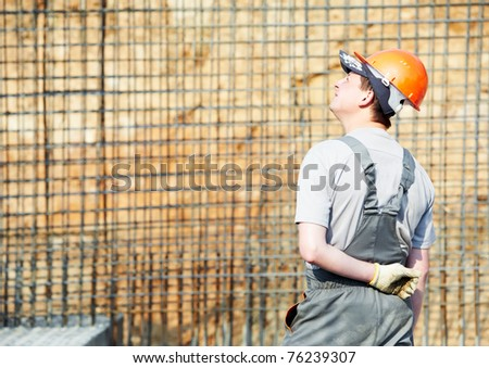 one builder worker in work wear and hardhat at construction site - stock photo