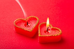 One burning candle and one with slight smoke. Symbolises the end of feelings of one person in the relationship, nonreciprocal love.