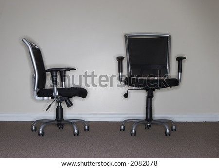 One business chair is facing and looking at the taller, more confident business chair, which is the boss
