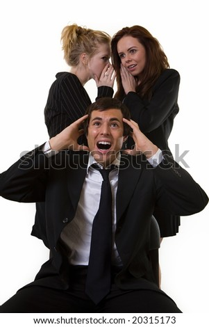 One business man with hands up and upset expression sitting at desk with two woman coworkers talking behind his back