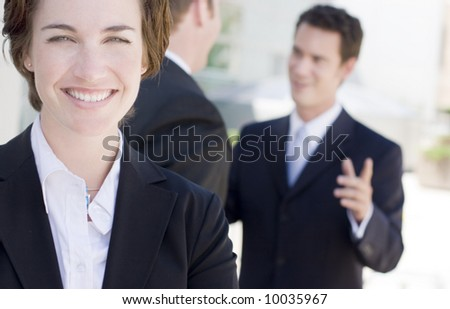 one business woman staring at camera while two businessmen talk in background