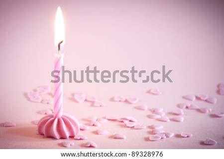 One candle on pink background with space for your text. See my portfolio for more