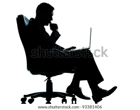 one caucasian business man computer computing serious sitting in armchair silhouette Full length in studio isolated on white background