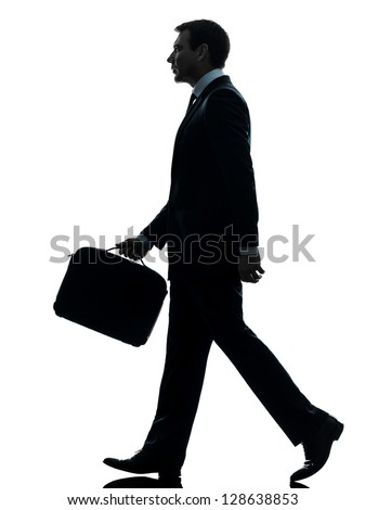 one caucasian businessman walking side view in silhouette studio isolated on white background - stock photo