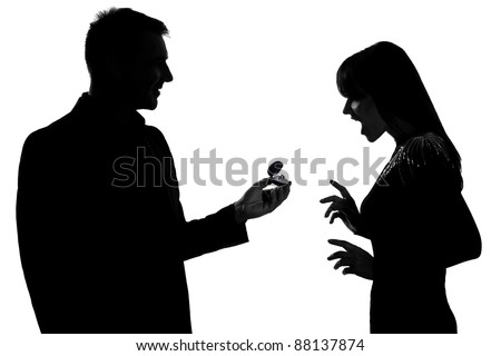 one caucasian couple man offering engagement ring and woman surprised in studio silhouette isolated on white background
