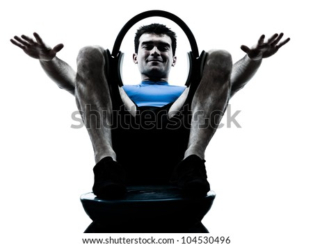 one caucasian man exercising pilates ring bosu workout fitness in silhouette studio  isolated on white background - stock photo