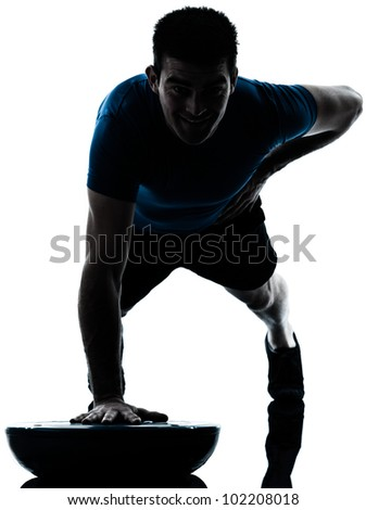 one caucasian man exercising push ups on bosu workout fitness in silhouette studio  isolated on white background