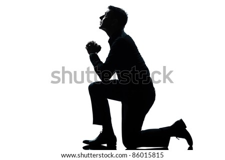 one caucasian man kneeling praying  full length silhouette in studio isolated white background