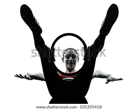 one caucasian woman exercising Pilates ring in silhouette studio isolated on white background