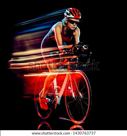 one caucasian woman triathlon triathlete cyclist cycling studio shot isolated on black background with light painting effect Foto stock ©