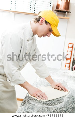 One chef baker in white uniform making bakery dough for pizza at kitchen