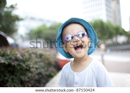 One chinese baby boy smiling at the city park