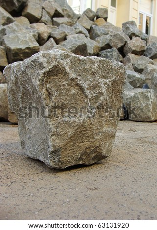 one 1 cobble stone laying in front of stack - stock photo