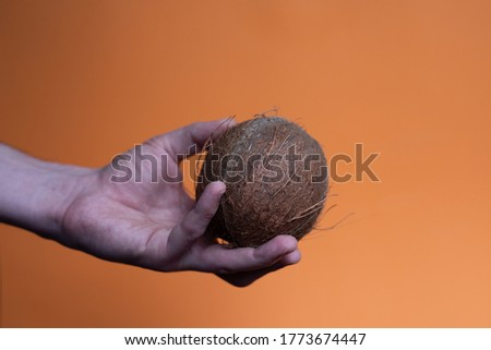 one coconut in a man's hand on an orange background