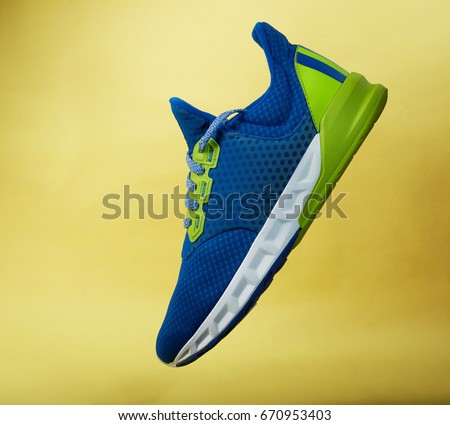 One colorful sneaker shoe isolated on yellow background fly in air