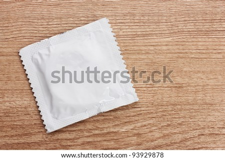One condom on wooden background