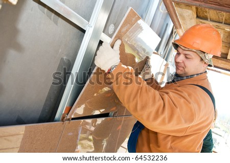 One construction worker builder installing big tile on a building facade