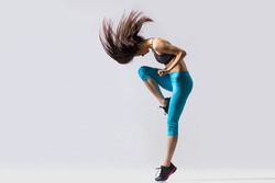 One cool beautiful young fit modern dancer lady in blue sportswear warming up, working out, dancing with her long hair flying, full length, studio image on gray background