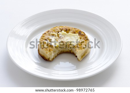 one crumpet on a plate with a bite taken