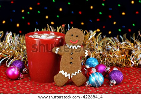One cup of cocoa with marshmallows and a standing gingerbread man cookie in a night setting.  Bokeh Christmas lights and ornaments.