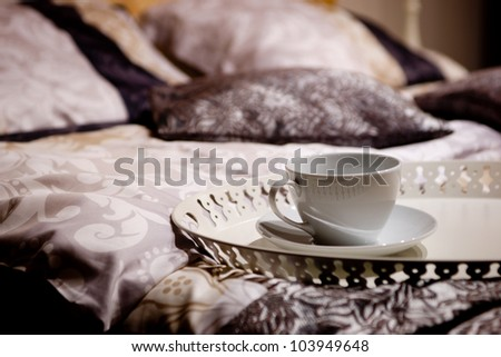 One cup on a nice bed