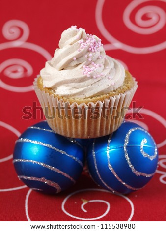 One cupcake and two christmas balls on red background