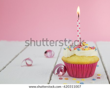 One cupcake with lit candle on white table against pink background - selective focus
