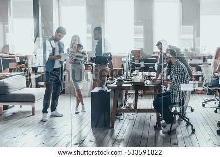One day in office. Group of young business people in smart casual wear working together in creative office #583591822
