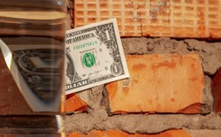 One dollar bill against a brickwork background, part of the bill is distorted through the prism of water and glass. Distorted vision, the idea of the dollar. Selective focus, close-up.