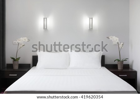 one double bed in a hotel near flowers on the nightstand #419620354