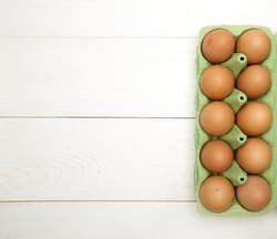 one dozen fresh chicken eggs lie in a paper cassette on a white wooden table.top view .selective focus. High quality photo