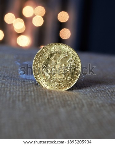 One ducat gold coin.  a small, gold coin as a way of investing capital.  ducat on a background of blurred lights. Bokeh in the background. Investing background Photo stock ©