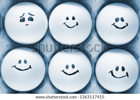One egg with sad emotion among another eggs with happy emotions. Eggs with emotions, toned. #1363117415
