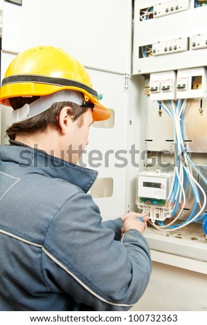 One electrician builder at work installing energy saving meter into electric line distribution fuseboard #100732363