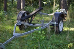 One empty single axle boat trailer with lodges front view near trees on forest parking at Sunny summer day, watercrafts transportation