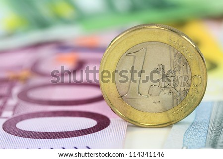 One euro coin against euro banknotes. Shallow DOF on euro coin - stock photo
