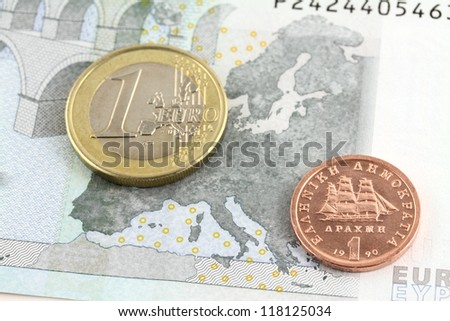 One euro coin and greek drachma over Europe map on five euro note. Shallow DOF on drachma