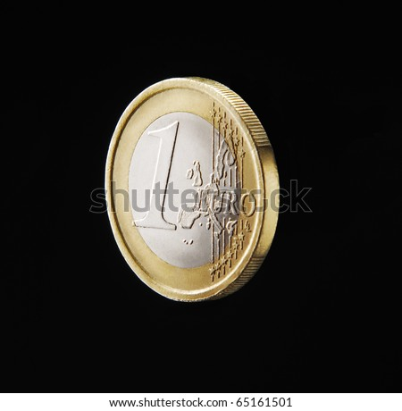 One euro coin isolated on black background.