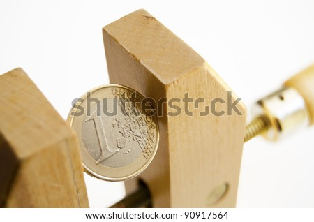 One euro coin under pressure in  a wooden clamp