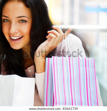 One excited shopping woman resting on bench at shopping mall looking at camera