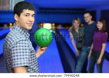 One fellow stands sideways and holds ball for playing in bowling and three friends hearten him, focus on  man