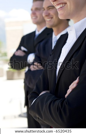 one female two males wearing business suits standing in a row smiling