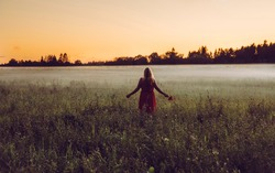 One feminine woman with long hair wearing orange dress and flowers on misty field in summer in sunset. Connecting with nature.
