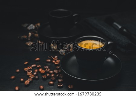 One filled espresso cup with visible crema, on a saucer surrounded by ingredients and utensils in a minimalist look Foto d'archivio ©