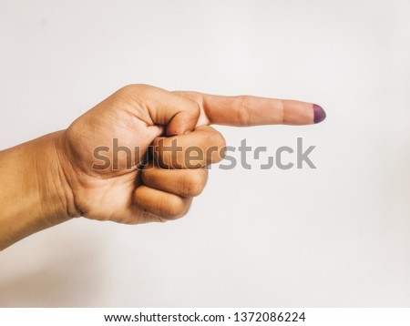 One finger or index finger of hands of a man who is isolated on a white background. Purple ink spots from the voters' fingers gave evidence of Indonesian elections. Sign for Jokowi supporter. #1372086224