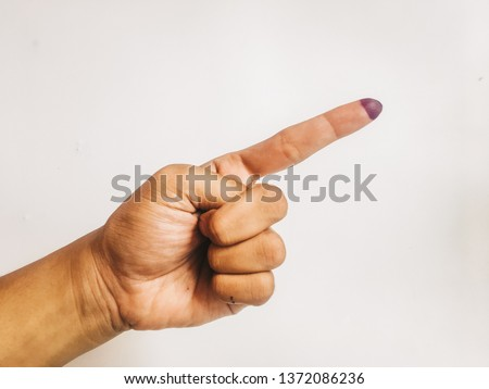 One finger or index finger of hands of a man who is isolated on a white background. Purple ink spots from the voters' fingers gave evidence of Indonesian elections. Sign for Jokowi supporter. #1372086236